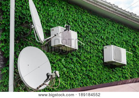 Antennas and air conditioners on a wall overgrown with grapes