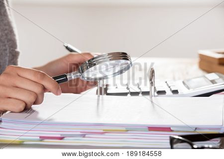 Close-up Of A Auditor Looking Invoice Through Magnifying Glass On Desk In Office