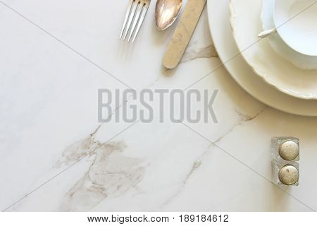 Simple monochromatic white table setting with vintage silverware and salt and pepper shaker. White marble copy space.