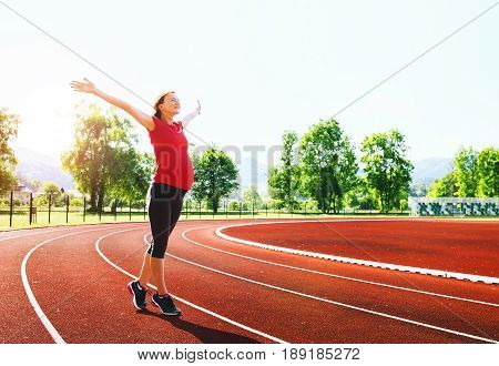 Happy pregnant sporty fitness woman with raised hands on red running track in stadium. Training stretching at summer outdoors on running track line. Sport healthy lifestyle while pregnancy concept.