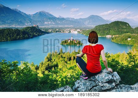 Travel Slovenia. Hiker on top of mountains. Woman Tourist looking on amazing Bled Lake with Church on Island Castle and Alps Mountain on background. Travel lifestyle concepts adventure vacations.