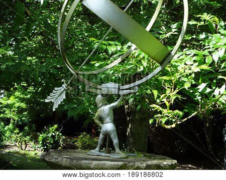 A garden statue, featuring an arrow, globe, and figure on a sunny day.