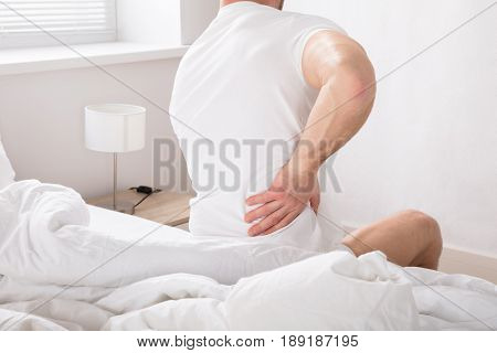 Rear View Of A Man Sitting On Bed Having Back Pain