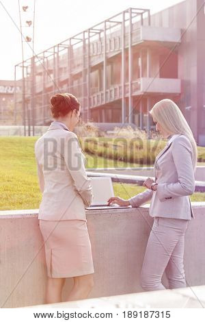Young businesswomen working together on laptop while standing against office building