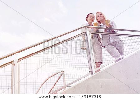 Low angle view of young businesswomen holding disposable coffee cups while standing by railing against sky