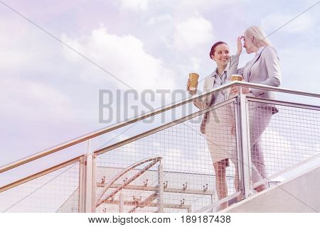 Young businesswomen with disposable coffee cups standing by railing against sky