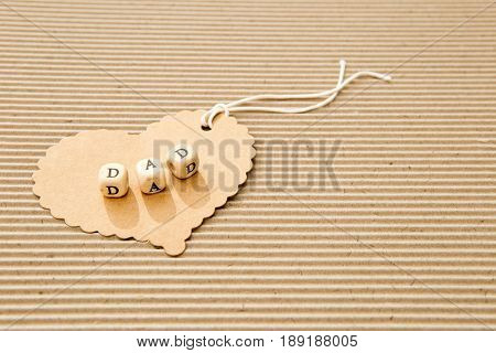 Father's Day - Dad on cardboard heart on corrugated cardboard background