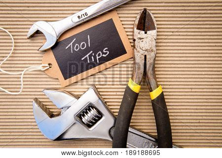 background - selection of tools on corrugated cardboard background with Tool Tips tag