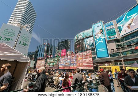 Toronto, Ontario, Canada, Dundas square down town, May 20, 2017, amazing gorgeous inviting view of many people at dundas square, walking, sitting, relaxing and enjoying their weekend time on sunny day