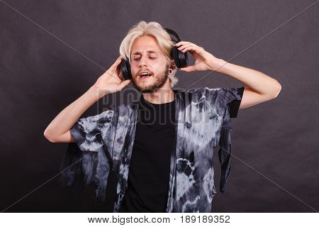 Music pasion male artist concept. Blonde man singing in studio wearing big black headphones. Indoor shot on dark grunge background