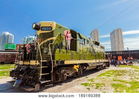 Toronto, Ontario, Canada, down town, May 20, 2017, nice amazing view of old style retro diesel train with little girl looking up in down town district area on sunny weekend day