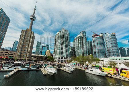 Toronto, Ontario, Canada, Harbourfront, down town, May 20, 2017, stunning gorgeous view of various yachts and boats parked on water, stylish inviting modern buildings, condos with people in background