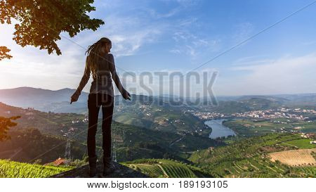Young woman with blond dreadlocks standing on the edge of a cliff and looks down at on the Douro Valley, Portugal. Looking from the top to Vineyards on a hills.