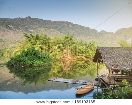 Bamboo raft in river with tree and mountain and blue sky in morningThailand