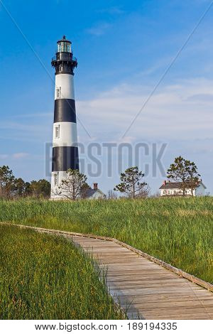 A wooden boardwalk leads through a marsh to the North Carolina's Bodie Island Lighthouse with its bold black and white stripes.