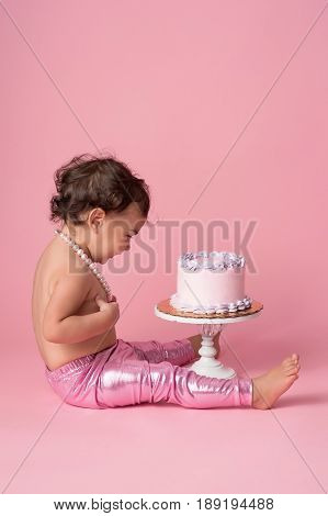 A profile view of a one year old girl sitting with a cake. She is wearing pink leggings and a string of pearls.