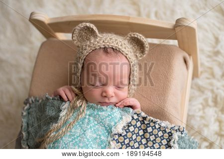 Two week old newborn baby boy wearing a tan crocheted bear bonnet. He is sleeping on a tiny wooden bed and covered with a blue quilt.