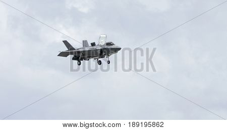 An F-35 Lightning hovers over cloudy sky background, military markings have been removed