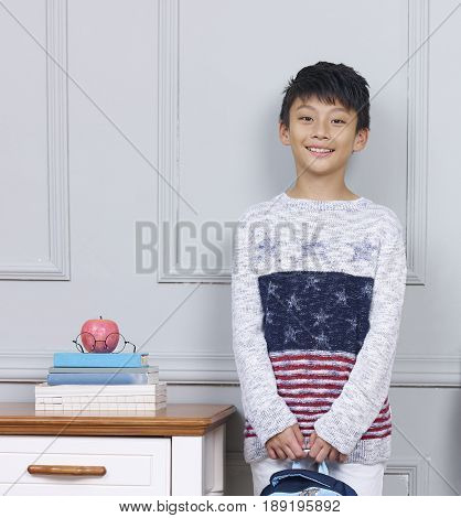 sunshine teenage Asian boy standing beside desk with book bag in hand
