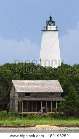 The Lighthouse and a beach house with shake siding are viewed from the water off Ocracoke Island part of North Carolina's Outer Banks.
