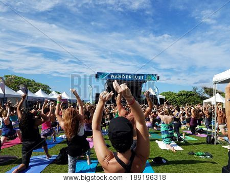 NORTH SHORE HAWAII - FEBRUARY 26: Yogi snap and move in Farewell: blissed and blessed yoga class a celebration of the power of yoga community music and nature outdoors with Mike love and Eoin Finn at Wanderlust yoga event on the North Shore Hawaii on Febr