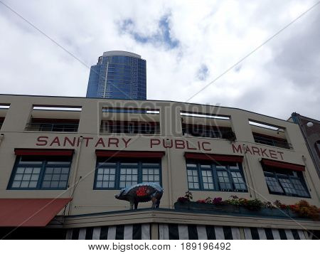 SeattleWashingtonusa. 06/25/16: Pike place Sanitary Public Farmers market sign with neon pig on side of building at during the day.
