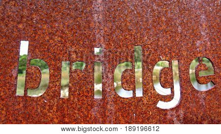 Rust rusted rusty metal cut-out word sign bridge building