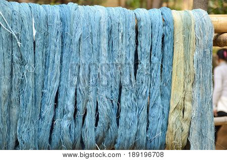 close up blue silk cocoons on bamboo wood