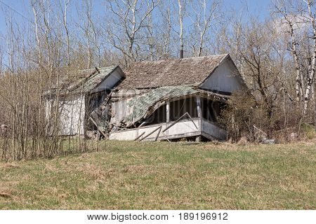 dilapidated house with a broken front porch