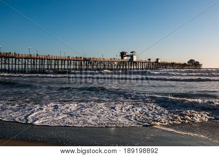 OCEANSIDE, CALIFORNIA - MARCH 23, 2017:  The Oceanside fishing pier in San Diego County, at 1954 feet, the longest wooden over-water pier on the West Coast.