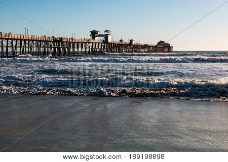 OCEANSIDE, CALIFORNIA - MARCH 23, 2017:  The landmark Oceanside fishing pier in San Diego County, the longest wooden over-water pier on the west coast.