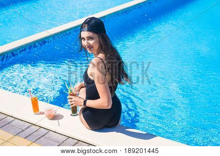 portrait of young sexy girl sitting at the edge of the swimming pool., wearing swimsuit and drinking cocktails during vacation. Pool party