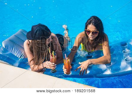 Party at smimming pool. Cheers. Group of cheerful girls on swimming mattress or air mattress in the swimming pool drinking cocktails and laughing