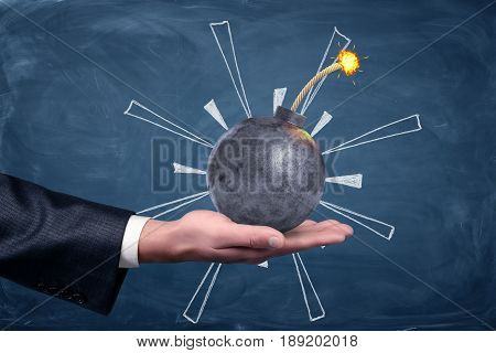 A male hand palm up holding a round iron bomb with a lit fuse on chalkboard background. Solve all trouble. Crisis management. Problem solving.