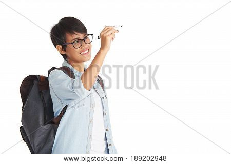 Smart Asian student in eyeglasses writing something in air with marker while standing against white background