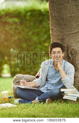 Handsome Asian student leaning elbow on pile of books while working on thesis in public park, full length portrait