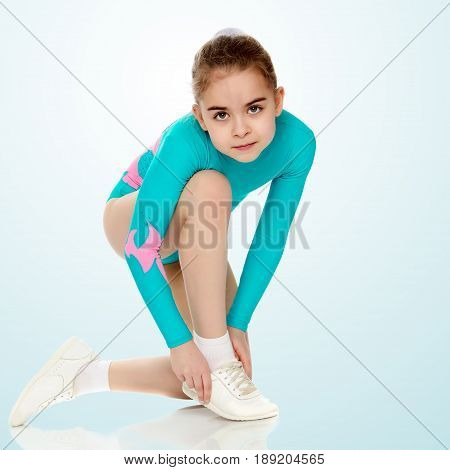 Very flexible little girl gymnast, junior school age, in a beautiful gymnastic swimsuit turquoise.She bent over to fix the shoes on her leg.On the pale blue background.