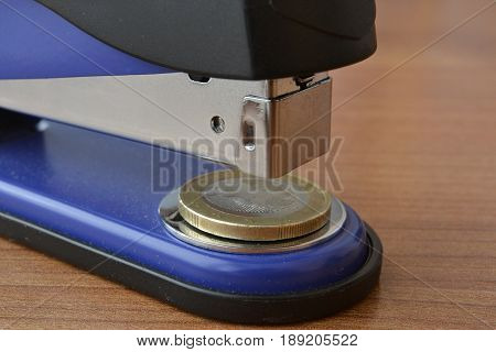 Business background with table stapler and euro coin.