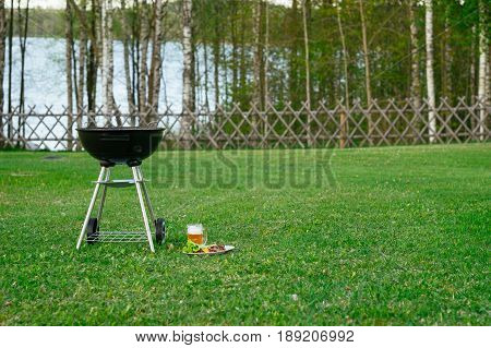 Barbecue grill beer and grilled vegetables in front of idyllic backyard with lake. Outdoor party on the holiday camp.
