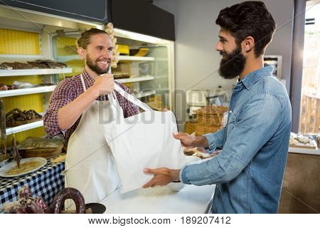 Staff giving parcel bag to customer at counter in shop