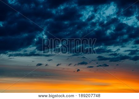 Dramatic sunset with vivid orange light and dark moody clouds