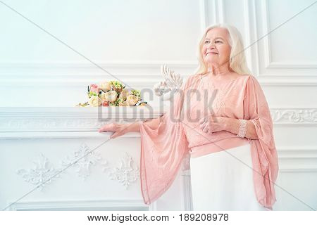 Modern well-groomed old woman with beautiful blonde hair standing in a room with a classic interior. Beauty, fashion. Luxury.