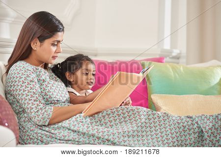 Indian mother and er little daughter reading together