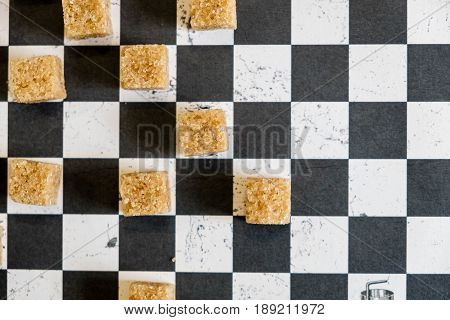 Background Of Sugar Cubes And Sugar In Spoon. Brown Sugar On Chess Background. Sugar With Copy Space