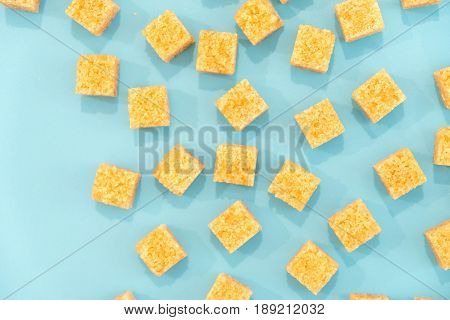 Background Of Sugar Cubes And Sugar In Spoon. Brown Sugar On Blue Background. Sugar With Copy Space.