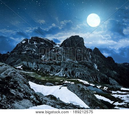 Mountain landscape in night sky with moon in Sexten Dolomites, South Tyrol, Italy.