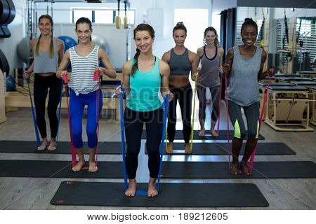 Portrait of fit women performing stretching exercise with resistance band in gym