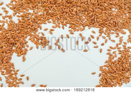 Some Linseeds Spread Out On Blue Background Seen From Above. Wooden Spoon. Close Up