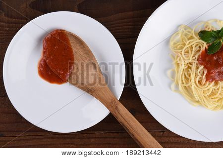 High angle view of a plate of spaghetti with marinara sauce and garnish. A second plate with a wood spoon and sauce in horizontal format.