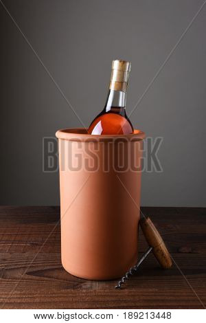 Terra cotta wine chiller on a rustic wood table. Vertical format with copy space.